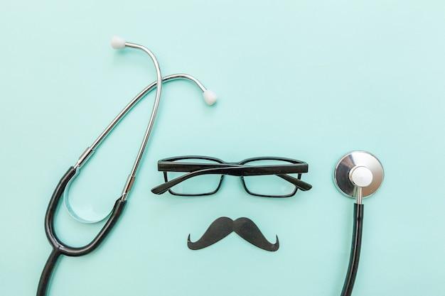 Eenvoudig minimaal ontwerp met geneeskunde apparatuur stethoscoop bril teken van snor geïsoleerd op blauwe achtergrond