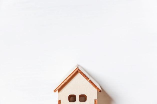 Eenvoudig minimaal ontwerp met miniatuur speelgoedhuis geïsoleerd op een witte achtergrond