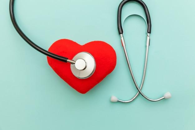 Eenvoudig minimaal ontwerp met stethoscoop en rood hart geïsoleerd op trendy pastelblauwe achtergrond