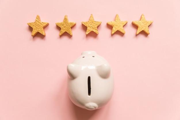 Eenvoudig minimaal ontwerpspaarvarken 5 gouden sterren die op roze achtergrond worden geïsoleerd