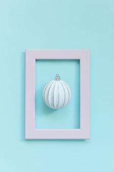 Eenvoudig minimale compositie winter objecten ornament bal in roze frame geïsoleerd op blauwe achtergrond