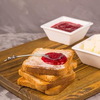 Eenvoudig ontbijt van traditionele producten - toast met boter en frambozenjam