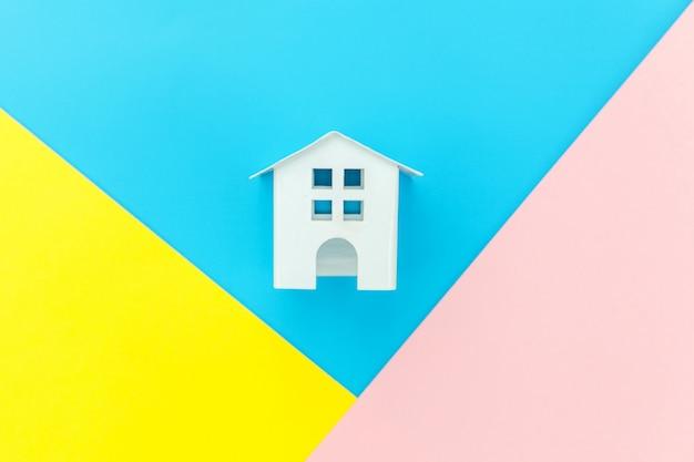 Eenvoudig ontwerp met miniatuur wit speelgoed huis geïsoleerd op blauw geel roze pastel kleurrijke trendy geometrische hypotheek eigendom verzekering droomhuis concept. plat lag bovenaanzicht kopie ruimte.