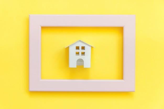 Eenvoudig ontwerpen met miniatuur wit speelgoedhuis in roze frame dat op kleurrijke trendy geel wordt geïsoleerd