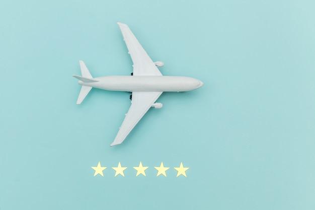 Eenvoudig plat lag model miniatuur speelgoedmodel vliegtuig en 5 sterren rating op blauwe pastel kleurrijke trendy achtergrond. reizen per vliegtuig vakantie zomer weekend zee avontuurlijke reis reis ticket tour concept.