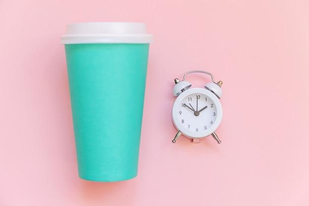 Eenvoudig plat lag ontwerp blauw papier koffiekopje en wekker geïsoleerd op roze pastel kleurrijke achtergrond