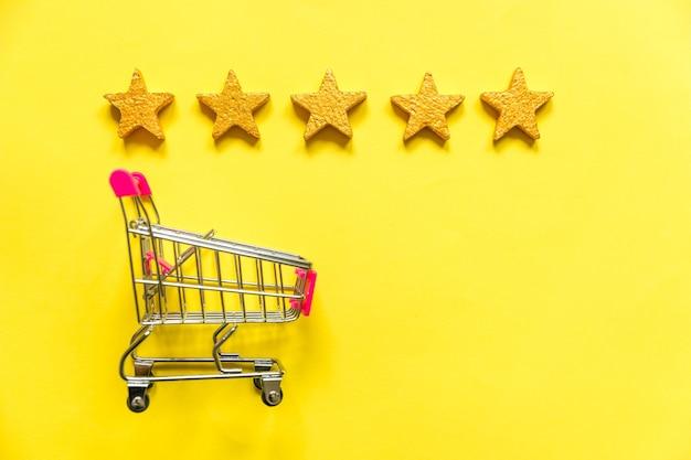 Eenvoudig plat ontwerp kleine supermarkt duwkarretje om te winkelen met wielen en vijf gouden sterren geïsoleerd op geel