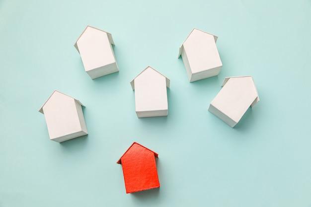 Eenvoudig plat ontwerp met miniatuur rood speelgoedmodelhuis tussen witte huizen geïsoleerd op pastelb...