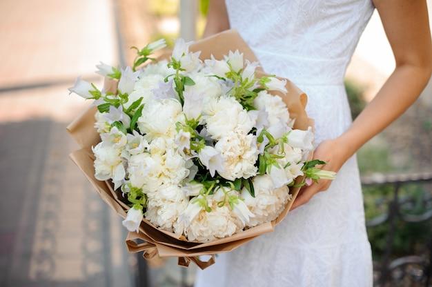 Eenvoudig wit huwelijksboeket in de handen van een vrouw