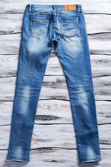 Eenvoudige blauwe spijkerbroek. achteraanzicht van casual jeans. dames denim broek op plank. nieuw kledingstuk voor een lage prijs.