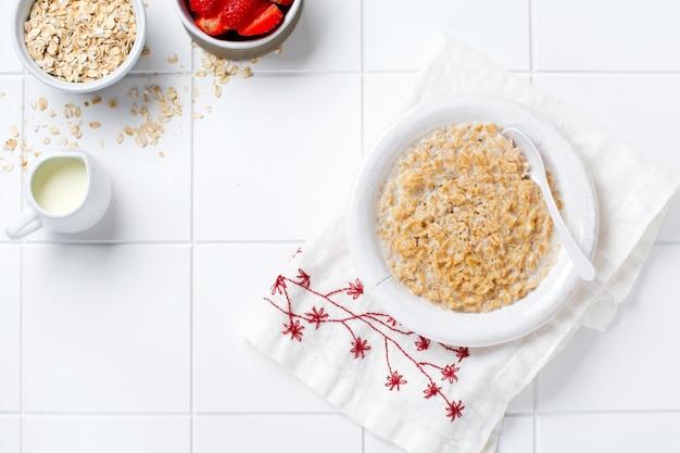 Eenvoudige havermoutpap met aardbeien in een witte plaat op een linnen servet. ontbijt gezondheidsvoedsel concept. bovenaanzicht