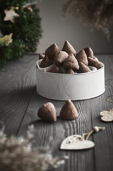 Eenvoudige kerst truffelsuikergoed op een houten tafel met plantentakken.