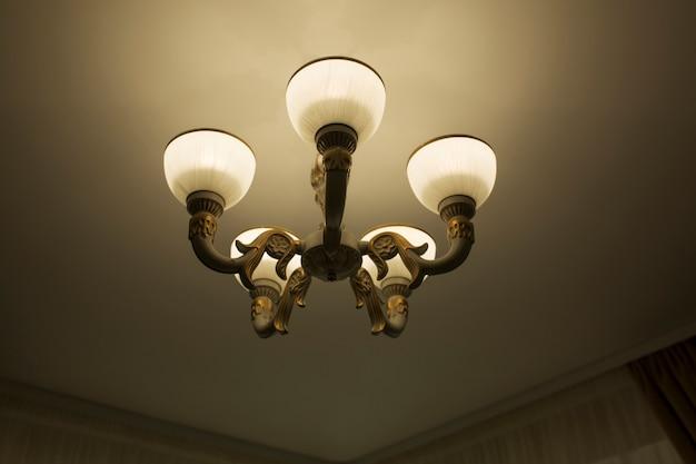 Eenvoudige kroonluchter op een wit plafond in een kamer