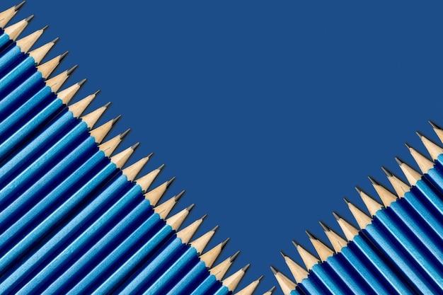 Eenvoudige potloden in het blauw op een blauwe achtergrond. potloden liggen schuin. achtergrond van blauwe klassieke kleur.