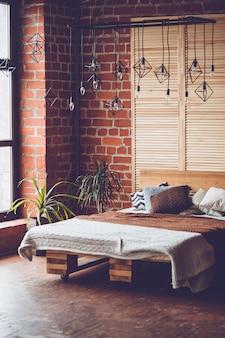 Eenvoudige slaapkamer met een tweepersoonsbed, een rode bakstenen muur en een groot raam