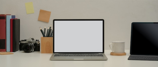 Eenvoudige studietafel met mock-up laptop, tablet met toetsenbord, potlood, notitieblok, camera, boeken en beker