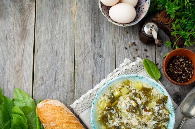 Eenvoudige vegetarische soep gemaakt van zuring, aardappelen en losgeklopte eieren op een oude houten achtergrond. selectieve aandacht. bovenaanzicht.
