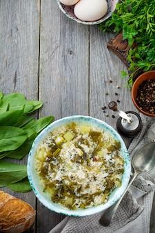 Eenvoudige vegetarische soep gemaakt van zuring, aardappelen en losgeklopte eieren op een oude houten ondergrond