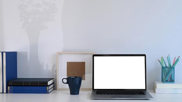 Eenvoudige werkplek met computer laptop, koffiekopje, boeken en briefpapier op witte tafel.
