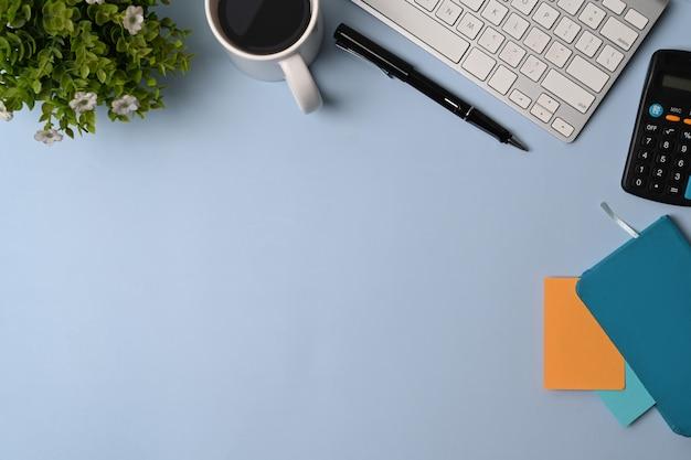 Eenvoudige werkplek met rekenmachine, notebook, bril, koffiekopje, toetsenbord en pen op blauwe achtergrond.