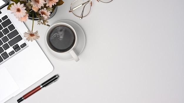 Eenvoudige werkruimte met laptopcomputer, koffiekopje en glazen.
