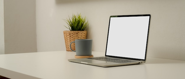 Eenvoudige werkruimte met mock-up laptop, koffiekopje, boompot en kopie ruimte op witte tafel