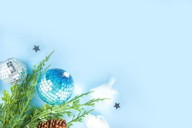 Eenvoudige xmas wenskaart, uitnodiging voor feest, verkoop abstracte flatlay met disco kerstballen, sparren takken, papieren zak met feestelijke strik, op lichtblauwe achtergrond kopie ruimte bovenaanzicht