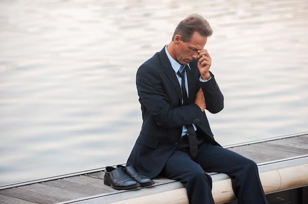 Eenzaam en depressief voelen. depressieve volwassen zakenman die zijn gezicht met de hand aanraakt terwijl hij op blote voeten aan de kade zit