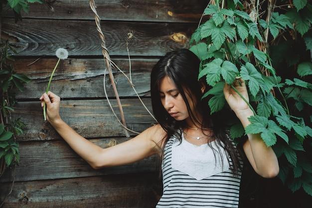 Eenzaam geïnspireerd meisje met blowballbloem dichtbij houten muur met groen. land meisje met paardebloem en meisjesachtige druivenbladeren in de lentetijd. mooi vrouwelijk portret.