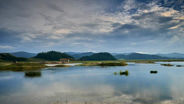 Eenzaam huis aan het meer in de bergen bij zonsondergang. altai