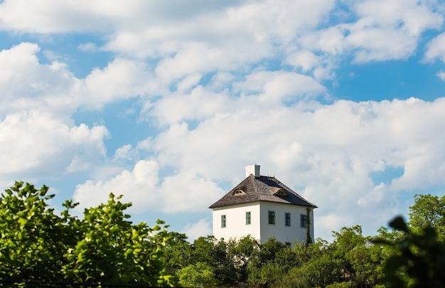 Eenzaam huis bovenop heuvel met blauwe hemel