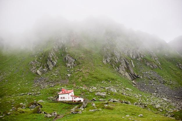 Eenzaam huis in de bergen van valleifagaras, transsylvanië, roemenië, europa. de bergen bedekten de mist.