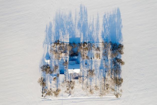 Eenzaam huis midden in een besneeuwd veld