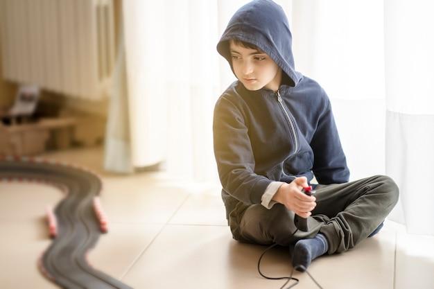 Eenzaam kind dat op de grond zit, speelt met een elektrische baan tijdens lockdown