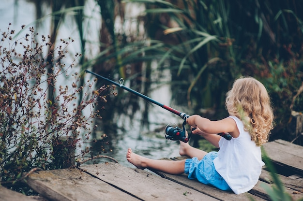 Eenzaam klein kind vissen van houten dok op het meer
