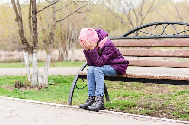 Eenzaam meisje huilen voor haar gezicht met handpalmen op een bankje. mentale gezondheid. tienerjaren
