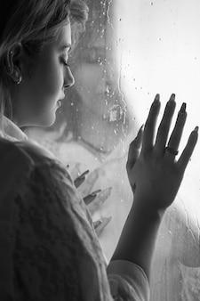 Eenzaam meisje in de buurt van venster na te denken over iets