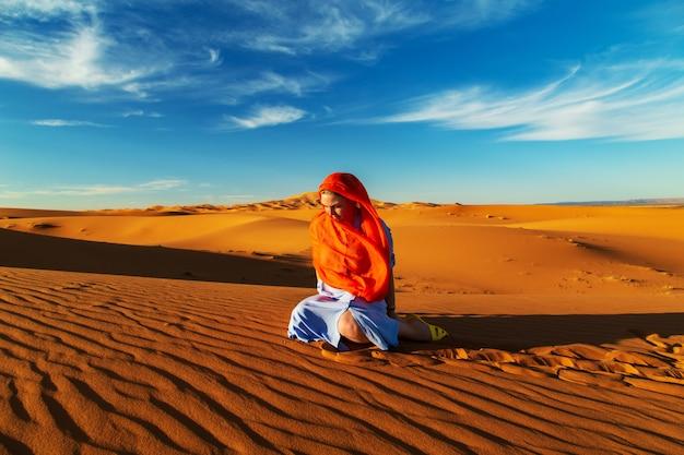 Eenzaam meisje in de sahara woestijn bij zonsondergang.
