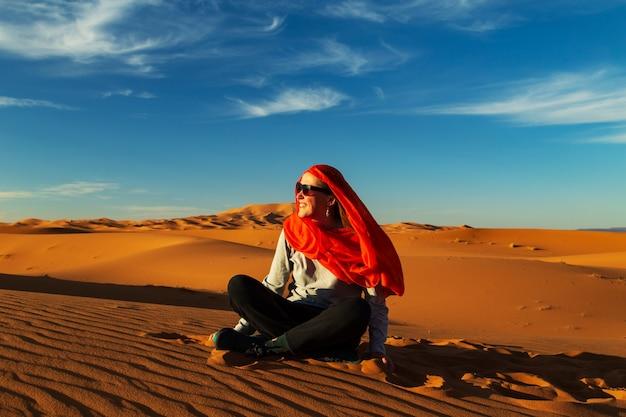 Eenzaam meisje in de saharawoestijn bij zonsondergang. erg chebbi, merzouga, marokko.