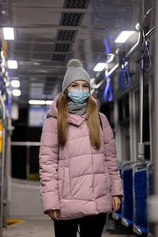 Eenzaam meisje met een gezichtsmasker rijdt 's nachts in een tram in pandemische tijd, polen