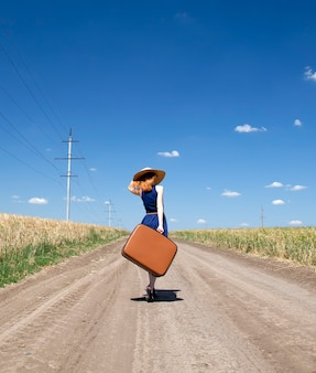 Eenzaam meisje met koffer bij landweg.