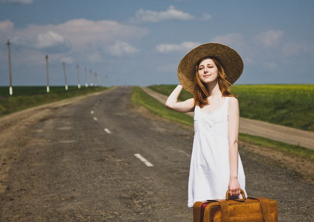 Eenzaam meisje met koffer bij landweg