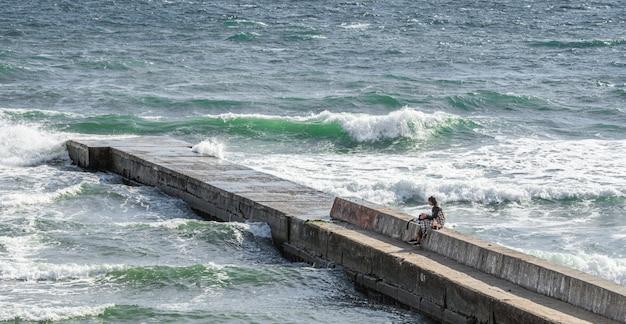 Eenzaam meisje op de pier rond de stormachtige zee