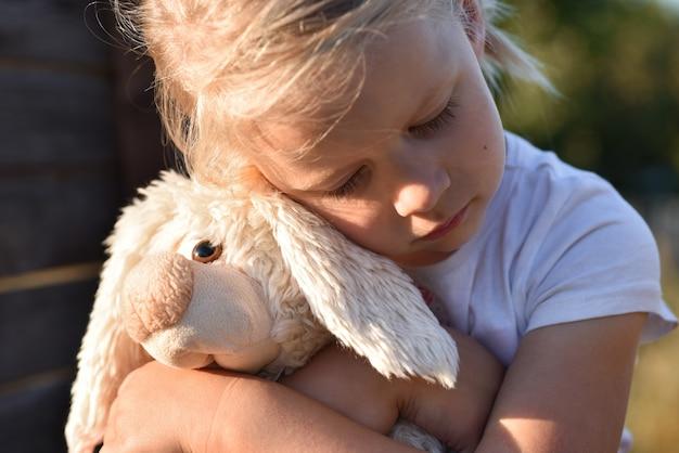 Eenzaam meisje op straat is verdrietig en houdt een speelgoedhaas met handen vast