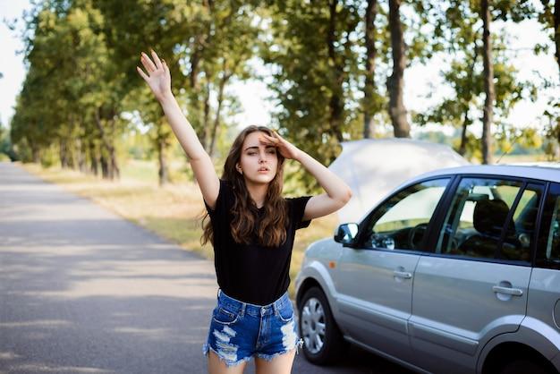Eenzaam meisje staat in de buurt van kapotte auto en stopt voorbijgangers om hulp te vragen