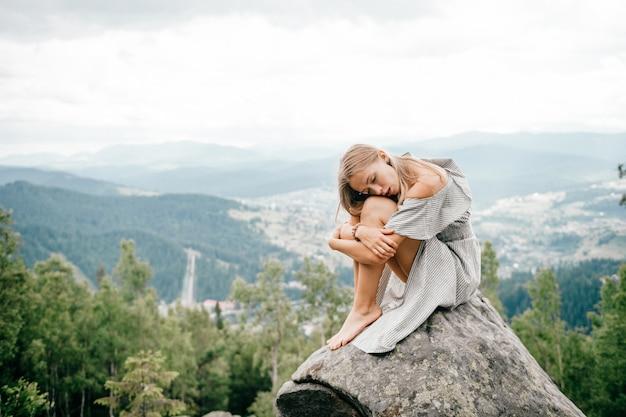 Eenzaam meisje zit op steen bovenop de berg