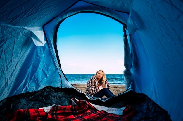 Eenzaam mooi blond meisje uit de tent op het strand voor alternatieve vrijheid kamperen in de open lucht. vakantie op het strand in de buurt van de golven van de oceaan voor surfer blonde meisje levensstijl californische manier