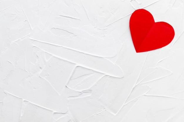 Eenzaam rood papperhart op witte stopverftextuur. valentijnsdag concept.