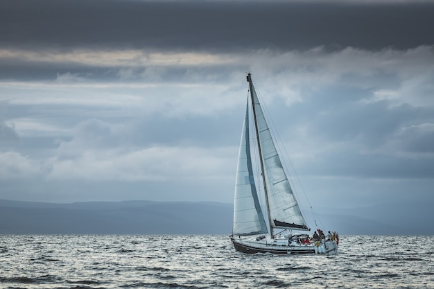 Eenzaam toeristisch jacht zeilen in de zee. donkere bewolkte hemel voor de regen. noord-ierland. verbazingwekkend zeelandschap het kleine schip onder het kalme water. oceaanlandschap in grijsblauwe tinten.