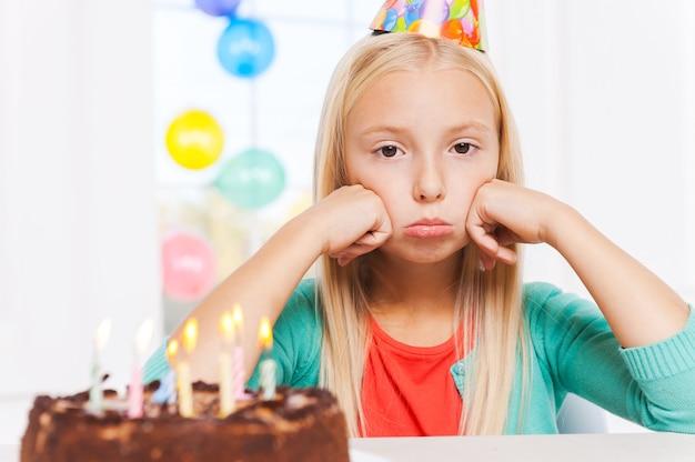 Eenzaam voelen op haar feestje. gelukkig klein meisje dat naar de verjaardagstaart kijkt en glimlacht